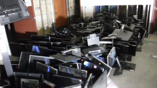 Dozens of computer screens sit on a concrete floor.