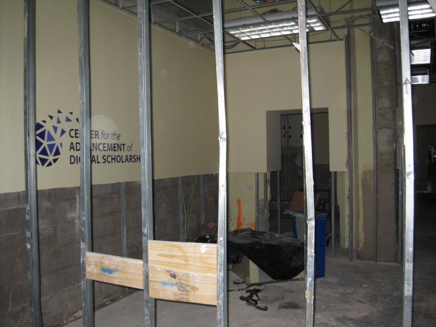 Dry wall has been removed, leaving only metal studs in its wake and exposing a wall sign for the Center for the Advancement of Digital Scholarship.