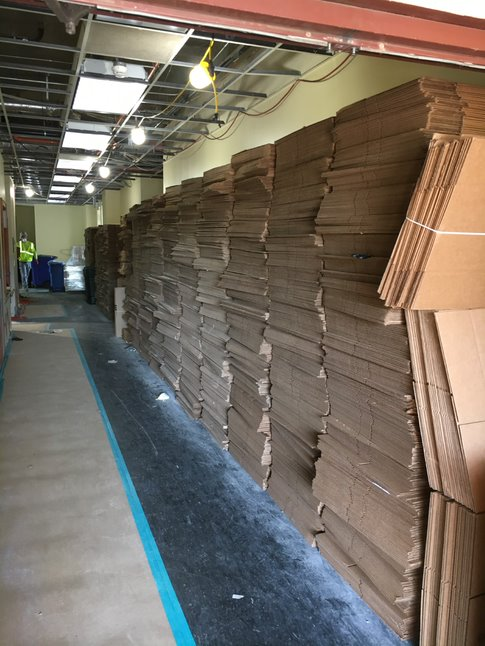 Rows of deconstructed cardboard boxes are lined up against the wall from floor to ceiling.