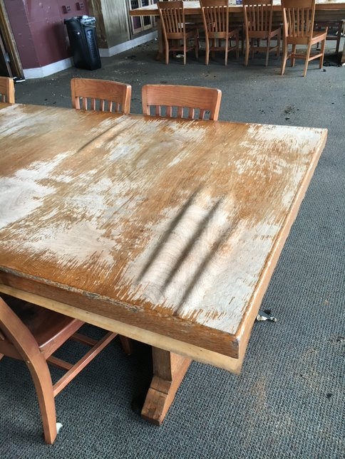 Brown wood tables are warped and wavy after severe water damage.