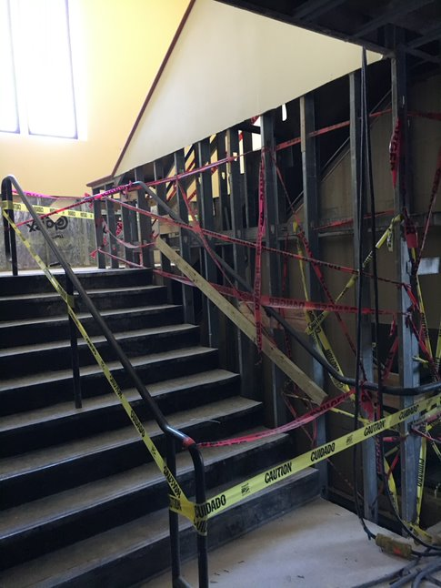 A stairwell is caution taped off with the side wall exposing metal studs and electric wiring.