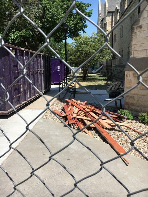 Looking through a metal chainlink fence lays brown baseboards next to purple dumpsters.