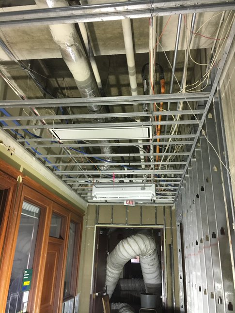 Ceiling tiles and grids are removed from a hallway, exposing pipes and electric wiring.