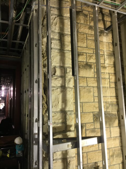 Dry wall has been removed showing a limestone wall behind metal studs.