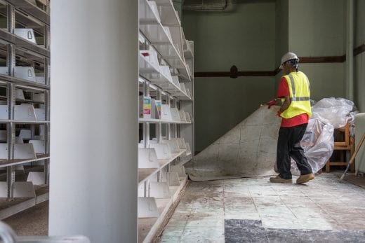 A Belfor worker in a yellow vests lifts up carpet next to white bookshelves.