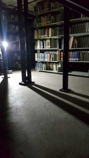 A dark room with metal beams, shelves with books, and cement flooring is lit up by a single bulb.
