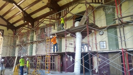 Workers construcing scaffolding along the murals in the Great Room.