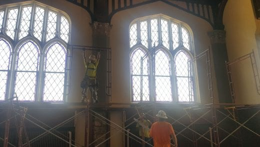 A Belfor worker builds scaffolding in front of the Ornamental windows in the Great Room.