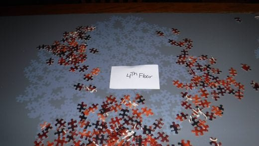 Red puzzle pieces on a dark blue table are scattered around to reveal light blue puzzle shapes left on the table.