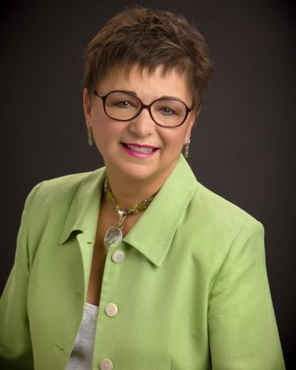 A headshot of a women with short brown hair, brown round glasses and a green button up shirt.