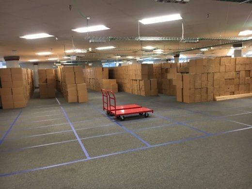 Blue tape lines the floor in grids and brown boxes are stacked in the boxes.
