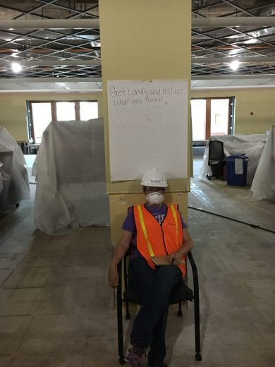 A woman in an orange vest and a white hard hat sits in a chair under a sign that reads get comfy and tell us what you think.