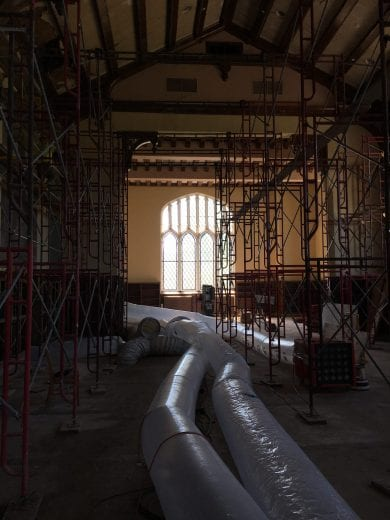 Large plastic tubes and metal scaffolding are back lit by a leaded glass window in the Great Room.