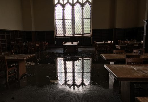 In a dimly lit room, the reflection of large leaded glass windows is visible in water pooled on the carpet.