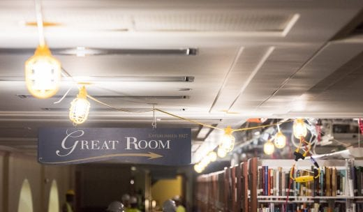 Near a Great Room sign on Hale Library's third floor, yellow construction lights are strung across the ceiling.