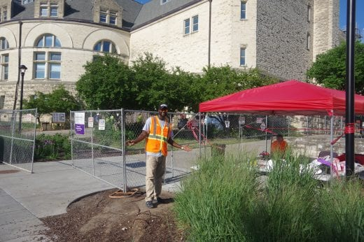 A Belfor worker in an orange vest in front of Hale next to a red tent.