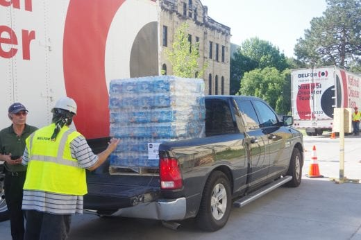 A pallet of bottled water sits in the back of a black truck.
