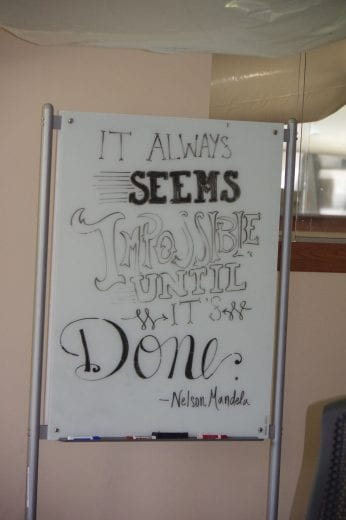 "A quote from Nelson Mandela on a white board that reads ""It always seems impossible until it's done."""