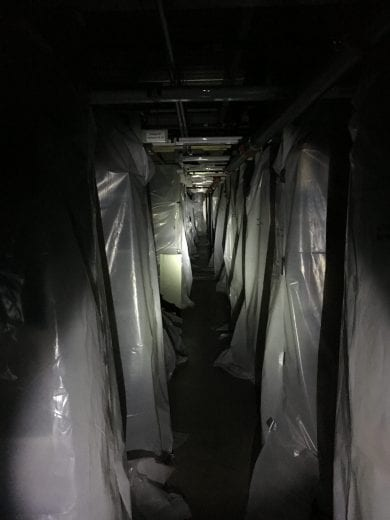 Rows of metal shelving draped in plastic are lit up by a flashlight.