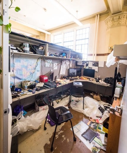 An employee's personal belongings, plastic sheeting, and debris litter an office cubicle.