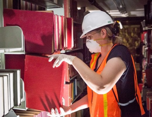 Woman wearing white hard hat, ventilation mask and neon orange emergency vest works by flashlight and pulls a large red book off of a bookshelf.