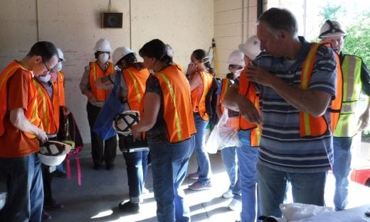 A group of twelve people dons orange emergency vests, hard hats and respirators.