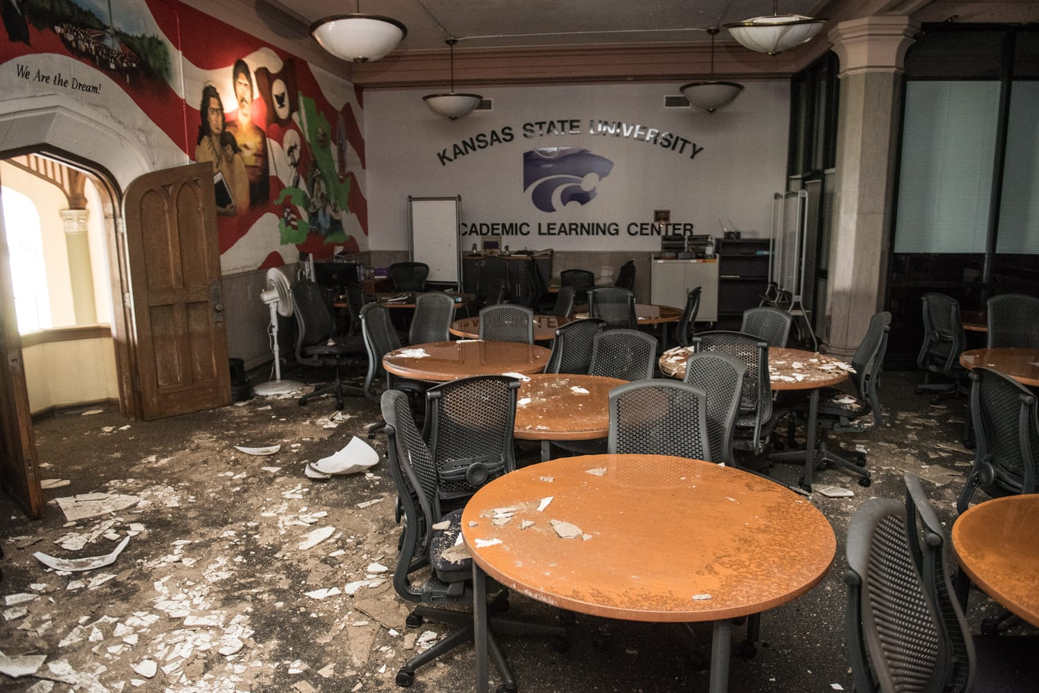 An interior scene of the Academic Learning Center with the mural on the wall at left. The carpet, half a dozen round wooden tables, and black office chairs are covered in plaster debris.