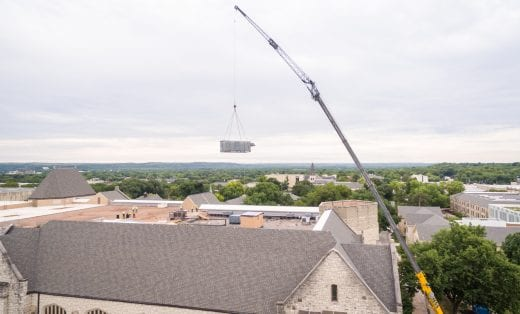 The metal arm of the crane extends high above the tan, peaked roof of the library as it lifts a large, rectangular piece of the HVAC unit.