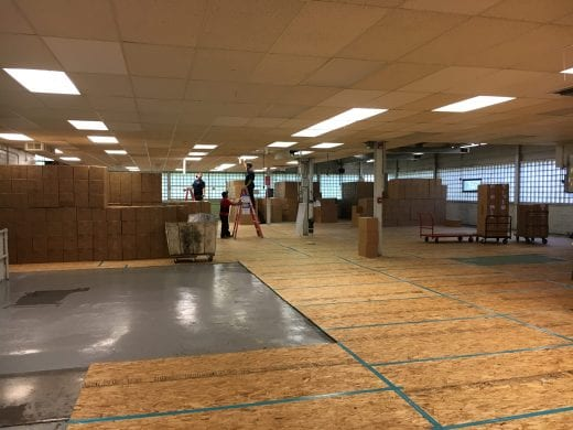 Inside Ag Press building with plywood floors and boxes of books.