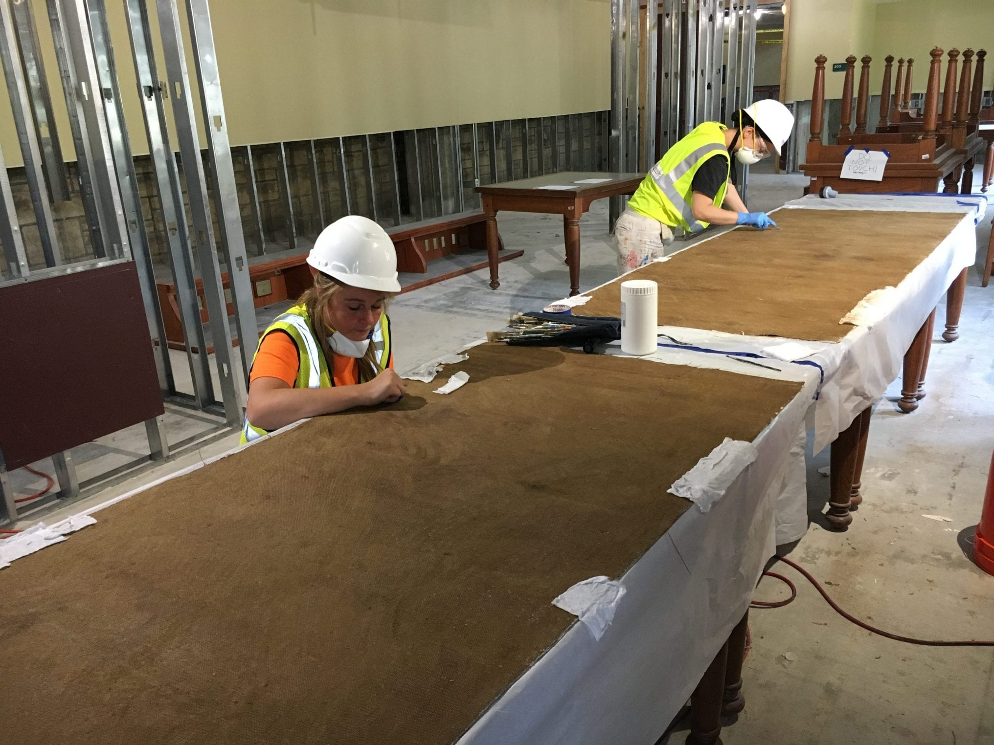 Two women wearing white hard hats and yellow construction vests lean over large brown rectangular panels of the murals spread on library tables so they can carefully remove debris.