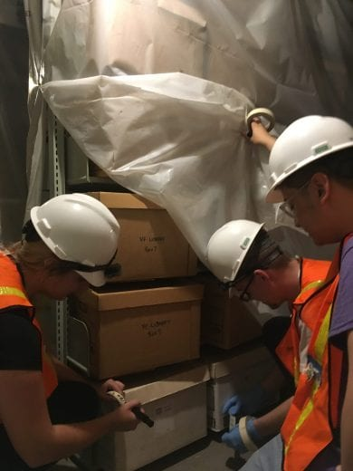 Students use flashlights to inventory boxes of special collections' material.