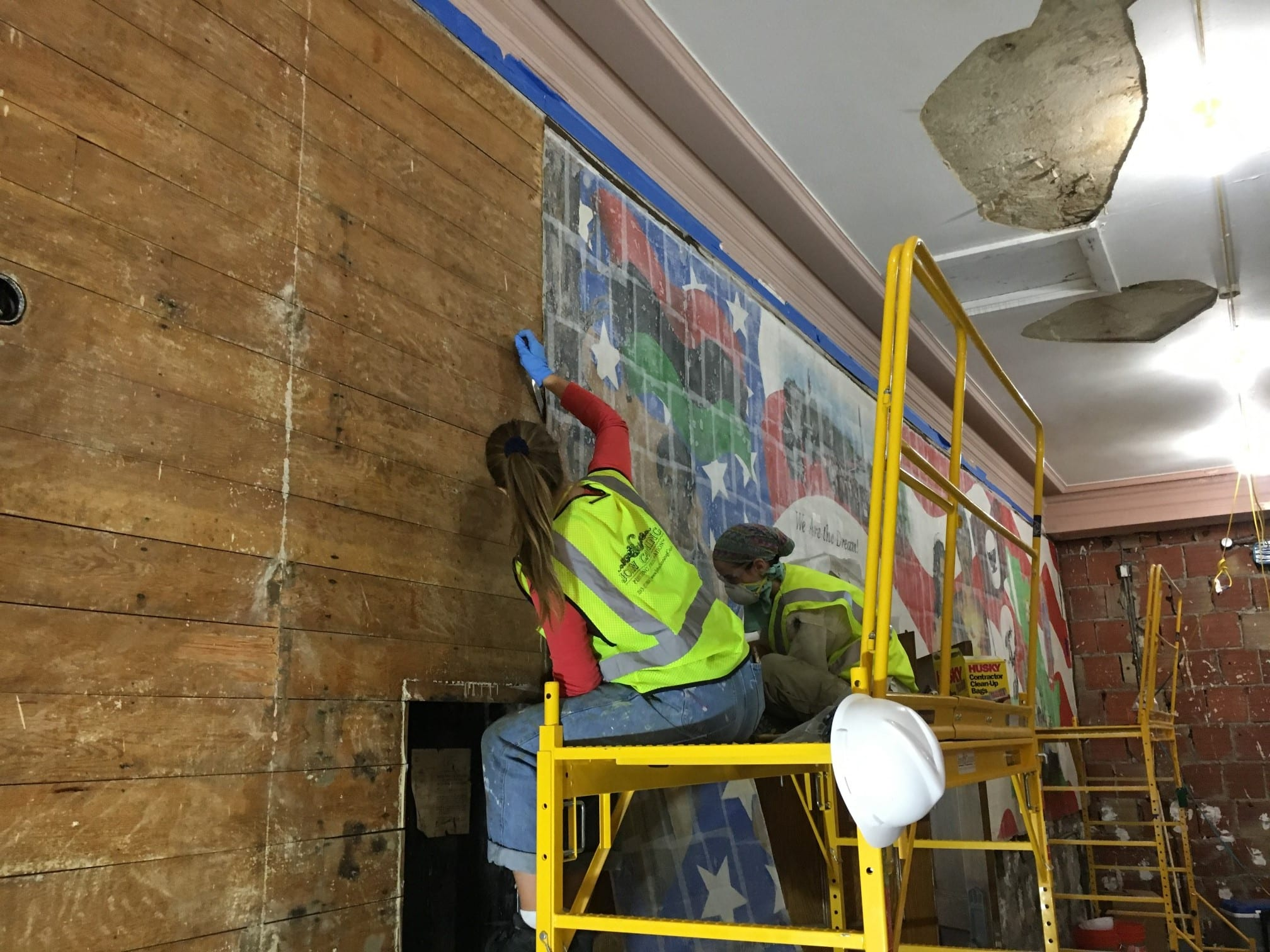 Two women in yellow construction vests sit on metal scaffolding as they remove a section of the mural from the wooden planks behind it that run horizontally across the length of the wall.