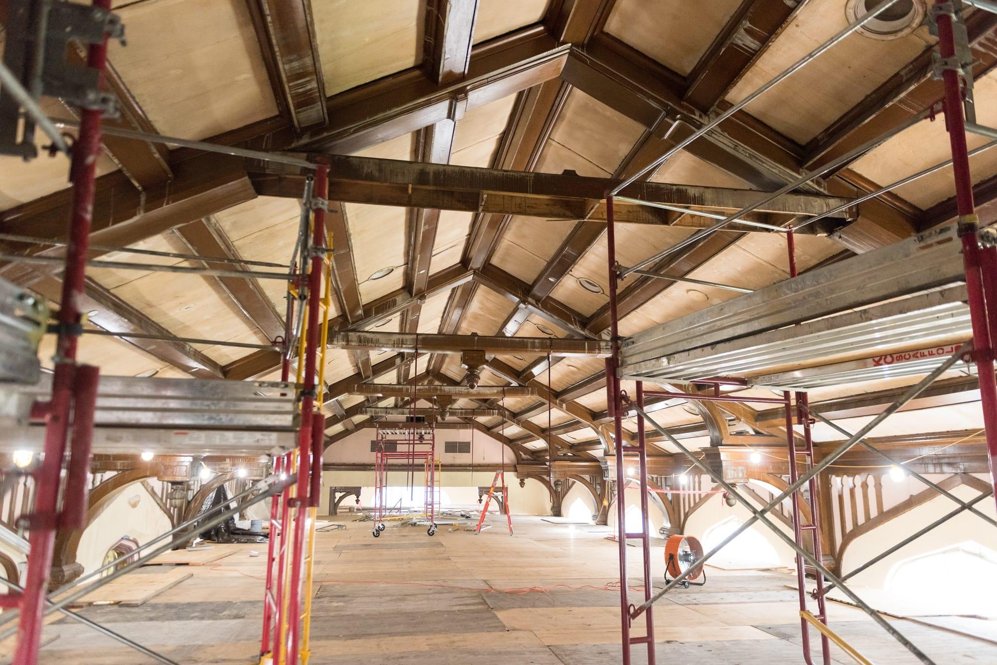 Some metal scaffolding sits on the elevated plywood floor directly under the Great Room's ceiling and wooden beams.