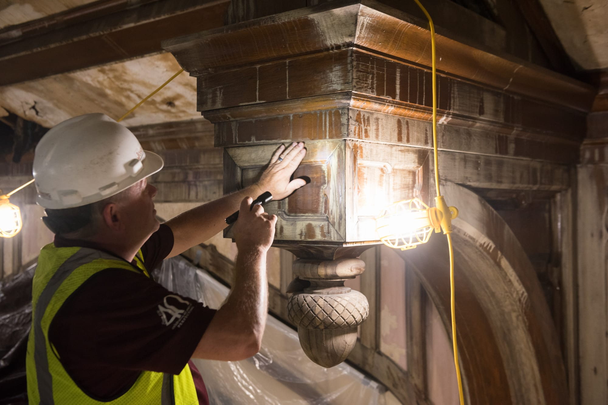 A man in a white hardhat and yellow construction vest faces a wood beam and examines it with a flashlight.