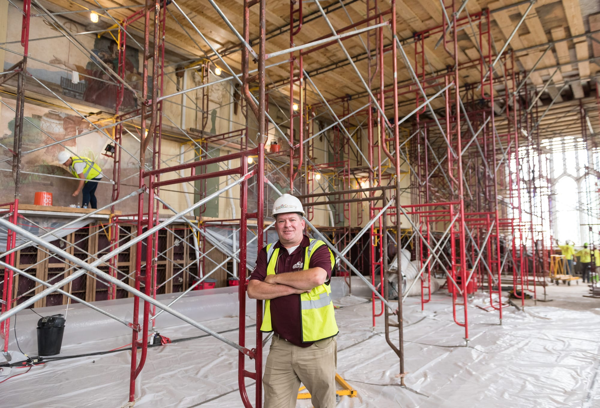 A man in a hardhat and yellow construction vest leans against red metal scaffolding in the Great Room.
