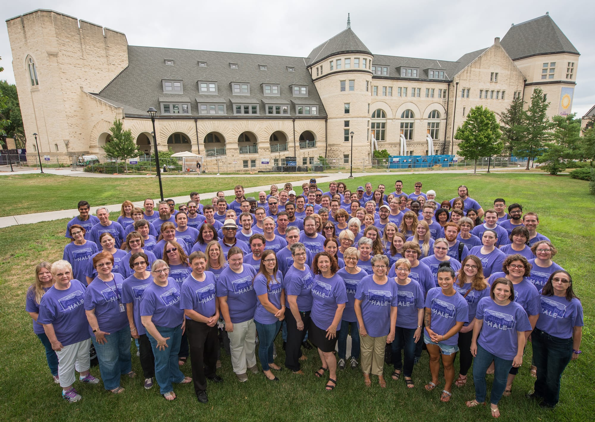 Nearly 100 employees wearing purple Hale Library t-shirts gather for a group photo on the grass in front of the Hale Library building.