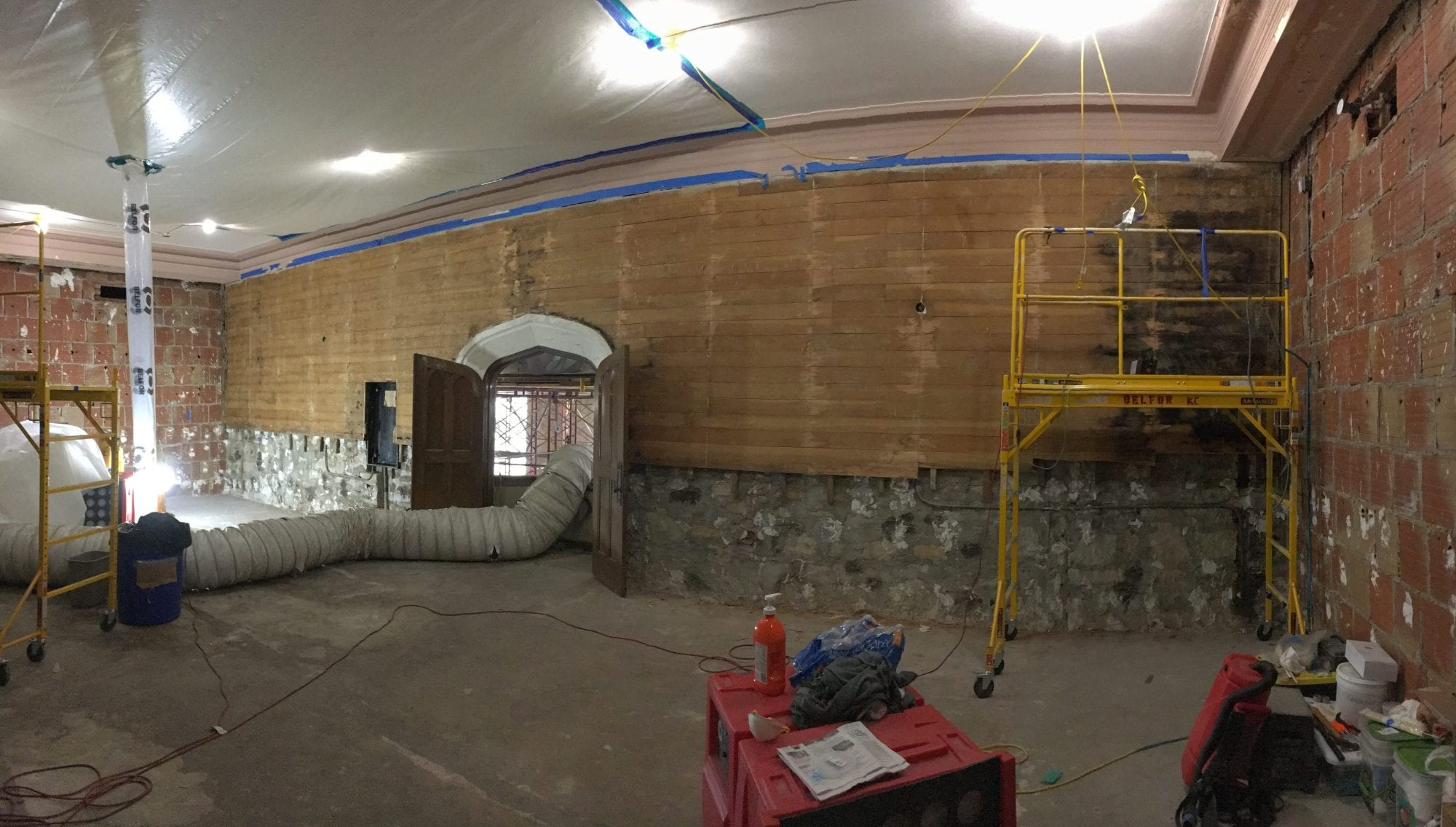 A panoramic shot of the room without the mural: Wooden planks run lengthwise along the top two-thirds of the wall while the bottom third is exposed stone.