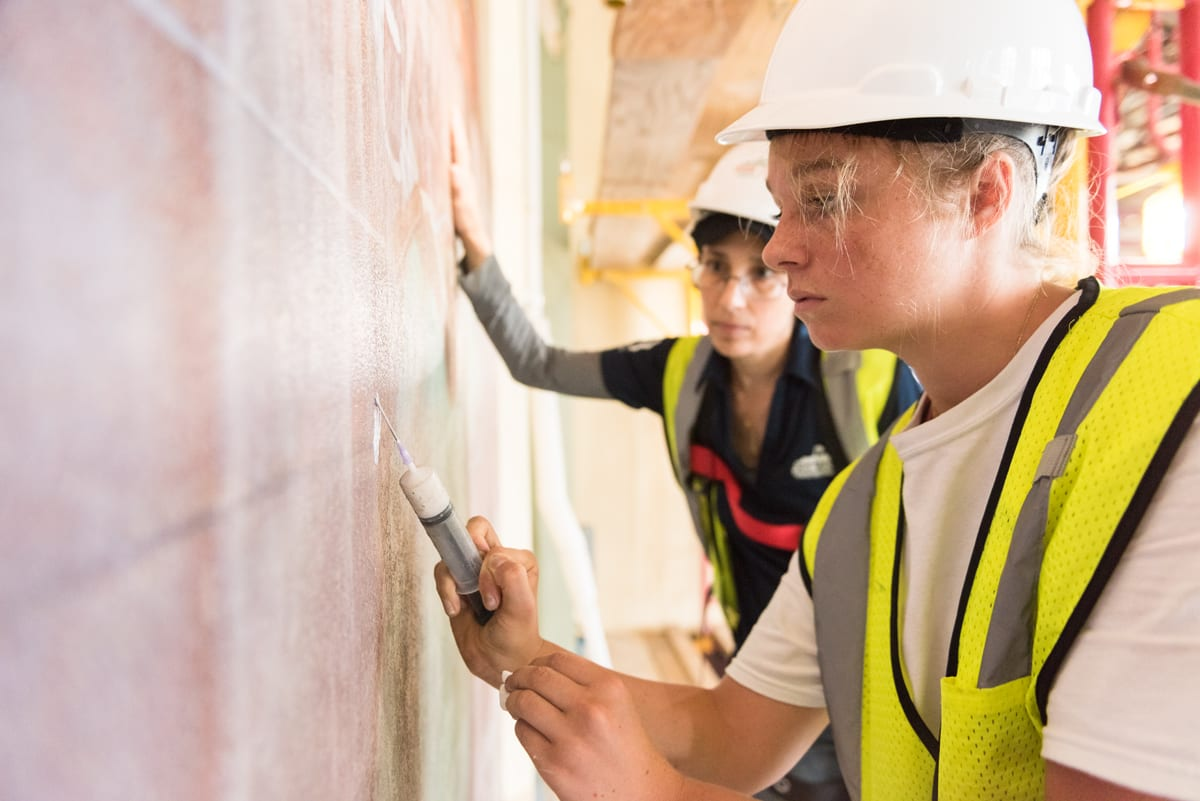 In the foreground at right, a woman wearing a white hard hat and yellow safety vest applies a white substance onto the wall at left, while in the background, another woman observes the process.