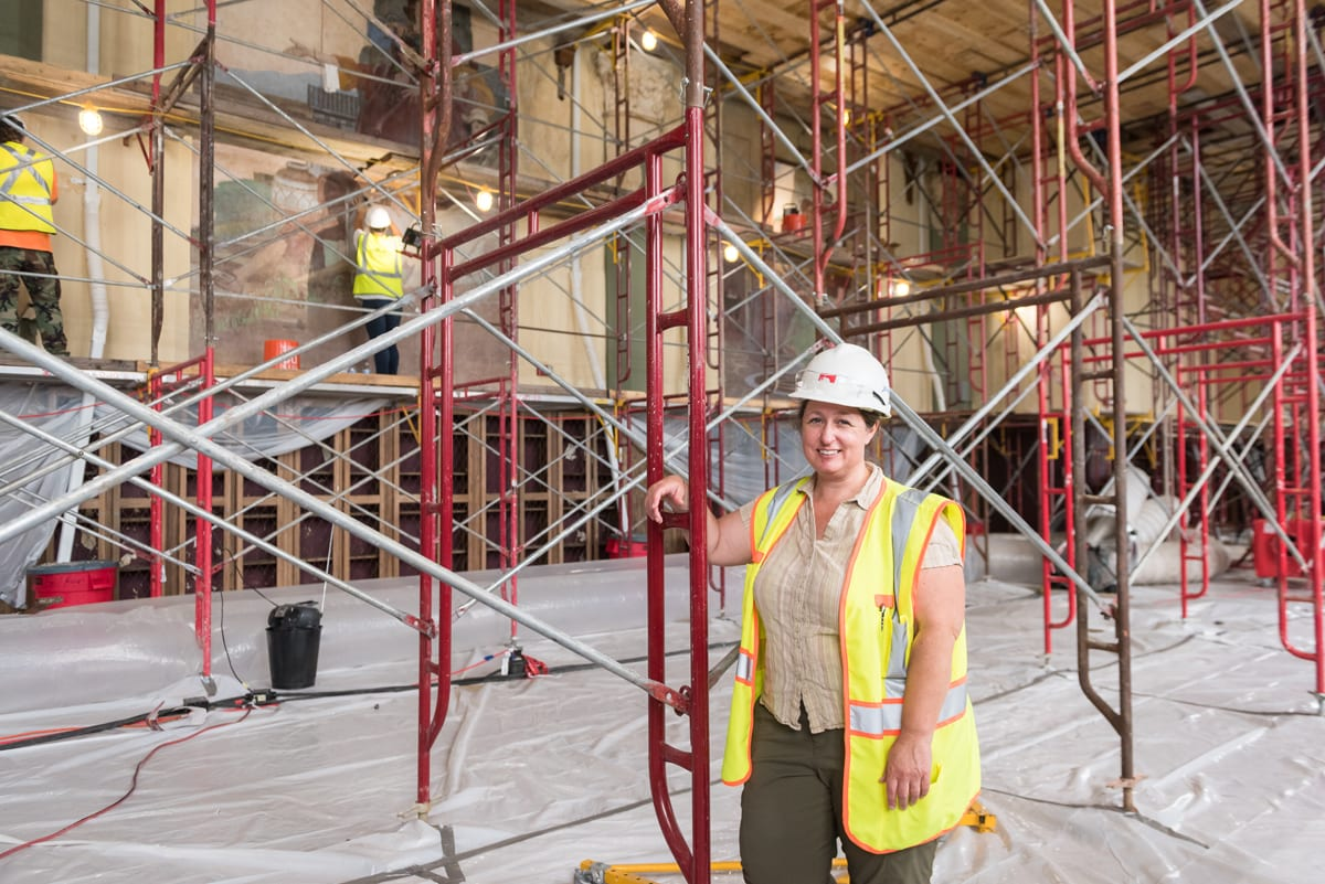 A woman with one hand resting on red metal scaffolding wears a white construction hat and a yellow safety vest. She stands in the foreground of the Great Room while workers in the background examine the murals on the walls.