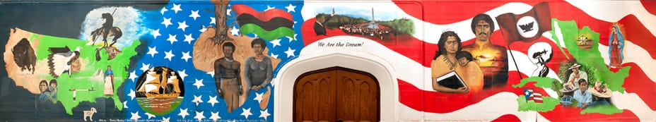 A full view of the mural, which features symbols of Native American culture, including a bison; images representing black American struggle such as Martin Luther King Jr. speaking on the Washington mall; and leading Hispanic activists such as Cesar Chavez. Stars and stripes from the U.S. flag form the backdrop.
