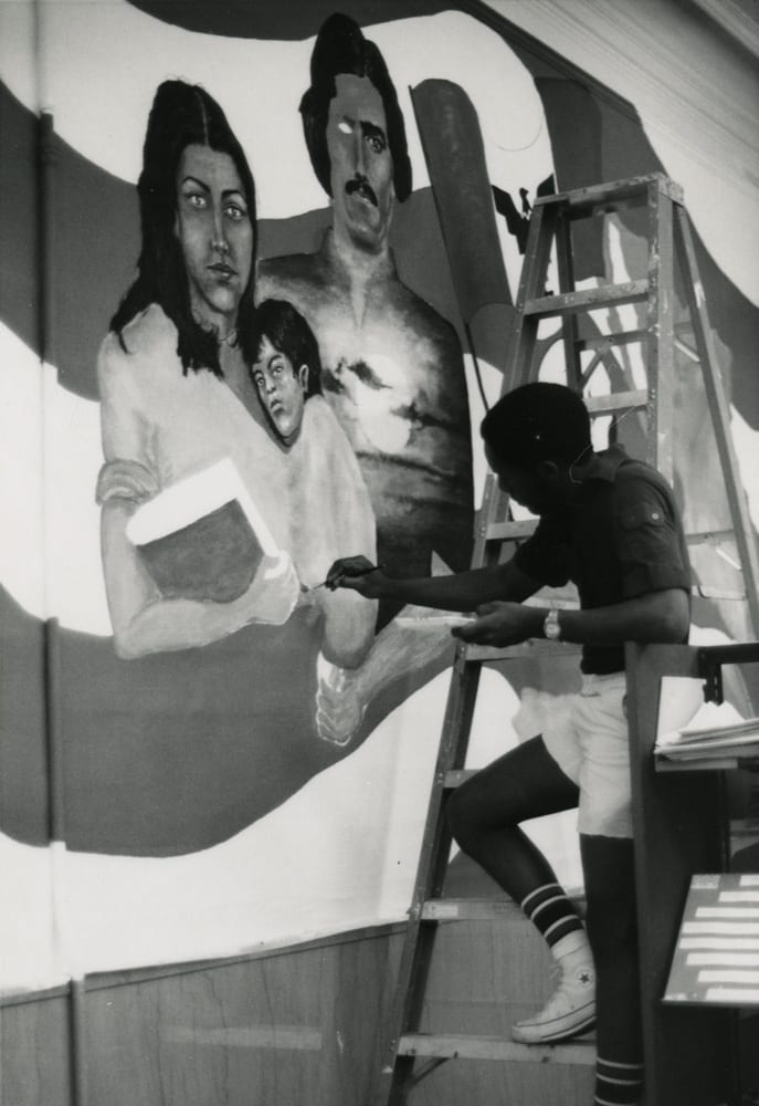 A man stands on a ladder at right with his hand outstretched to work on portraits of a Hispanic family that are featured in the mural.