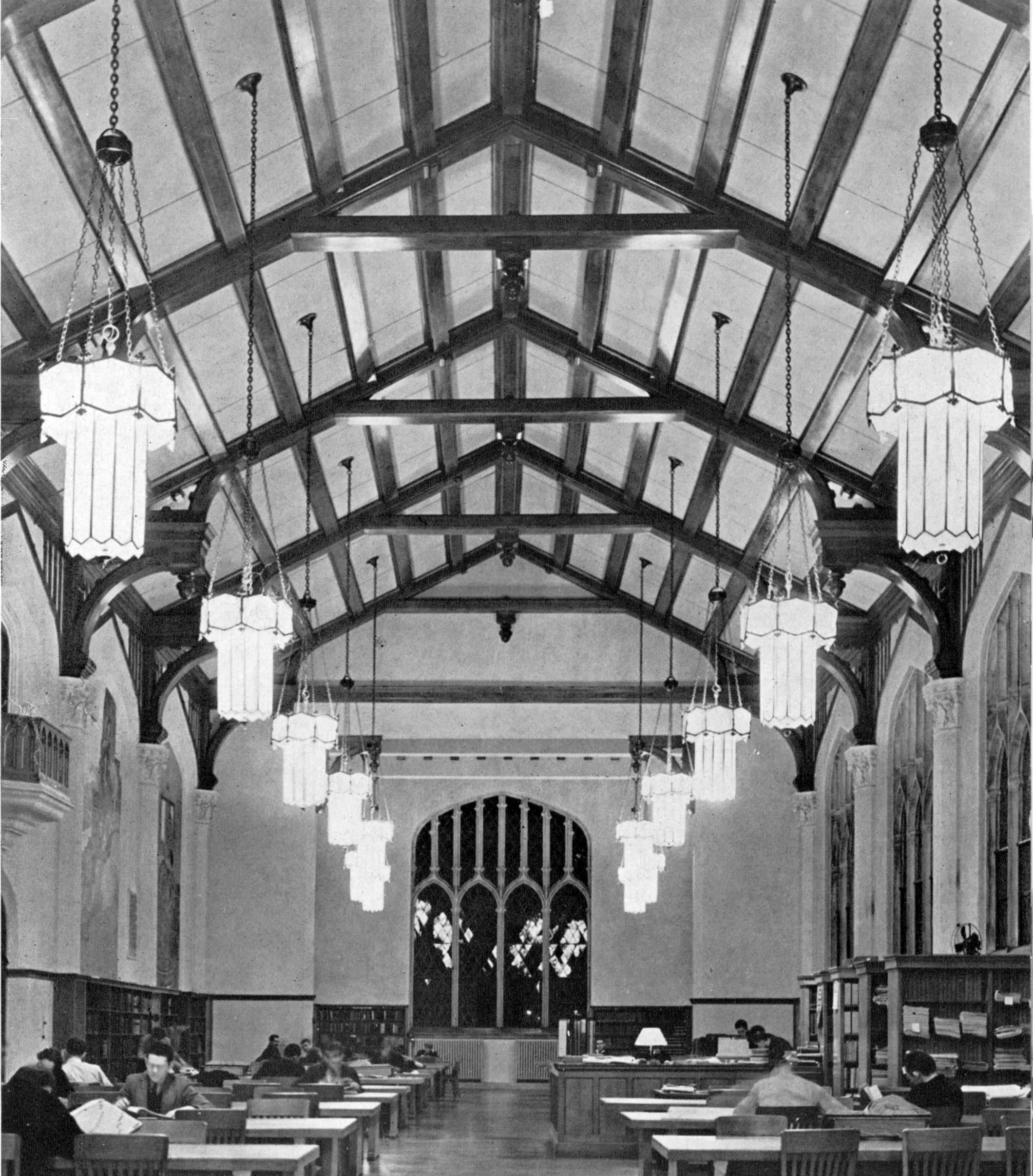 In a vintage black-and-white photo of the Great Room, students study at large wooden tables. The building's heavy wooden ceiling beams, ornate light fixtures, and leaded glass windows are visible.