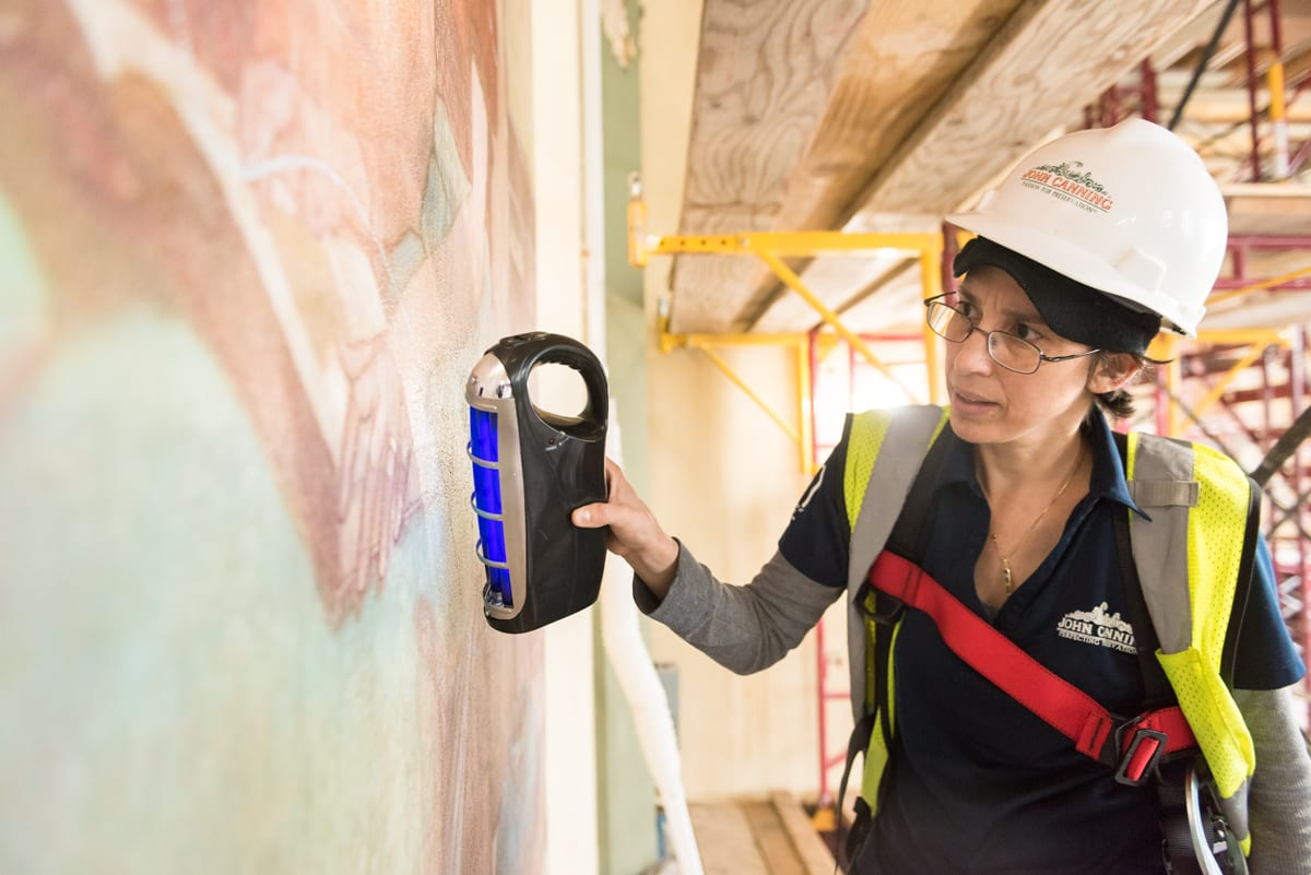 At right, a woman wearing a white hard hat scans the surface of a mural with a hand-held black light device.