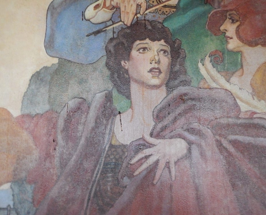 "In a detail from the art deco style ""Arts"" mural, an actor in flowing maroon robes extends one arm while the other hand is wrapped around his torso in a dramatic gesture."