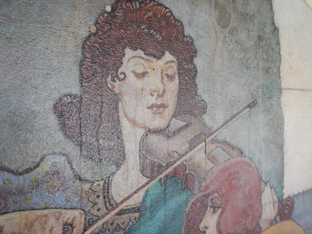 "Close-up of the streaking on the surface of the ""Arts"" Great Room mural which features a female violinist with shoulder-length brown hair."
