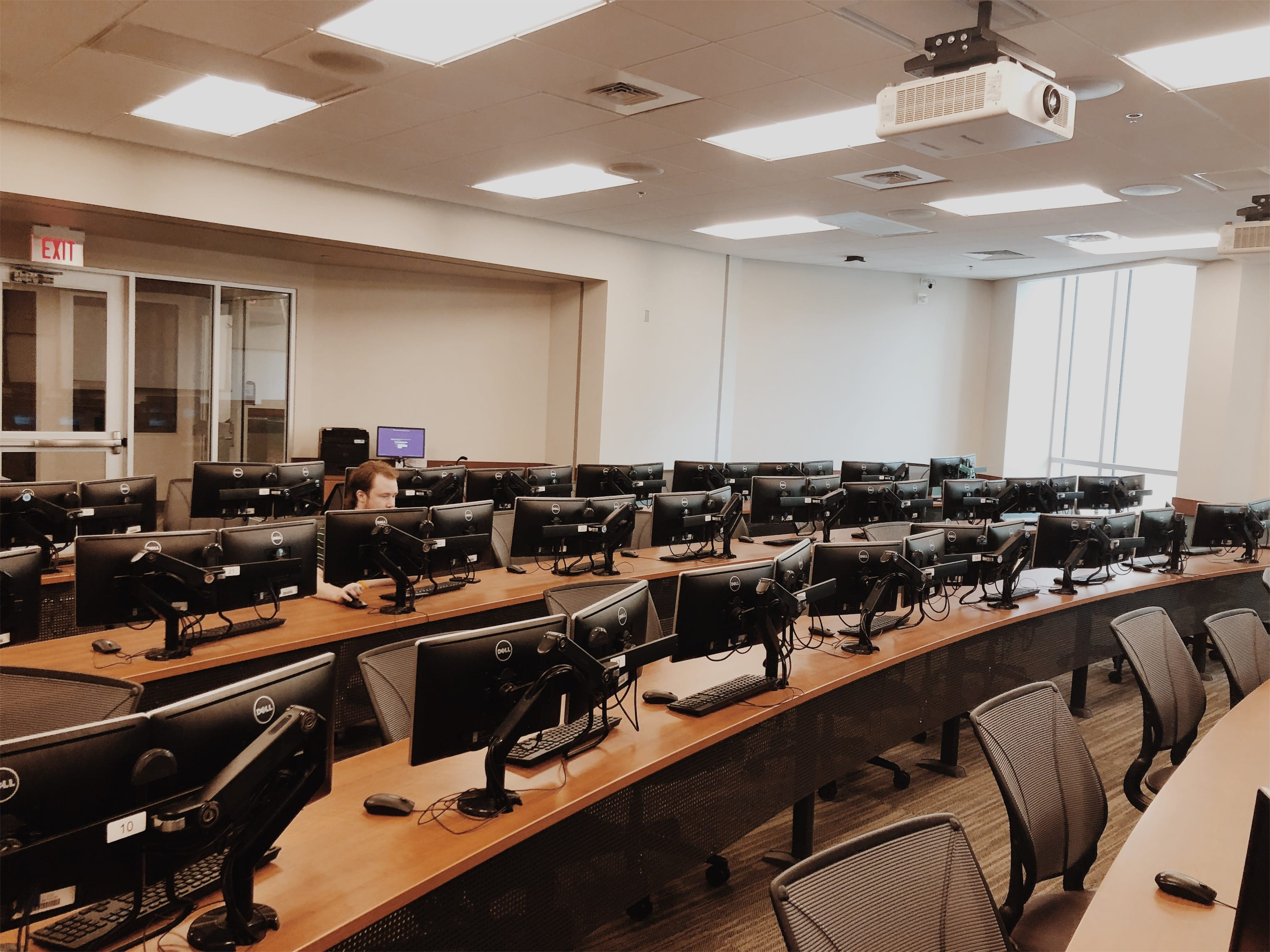 More than two dozen double computer monitors line long wooden tables in a room occupied by a single student.