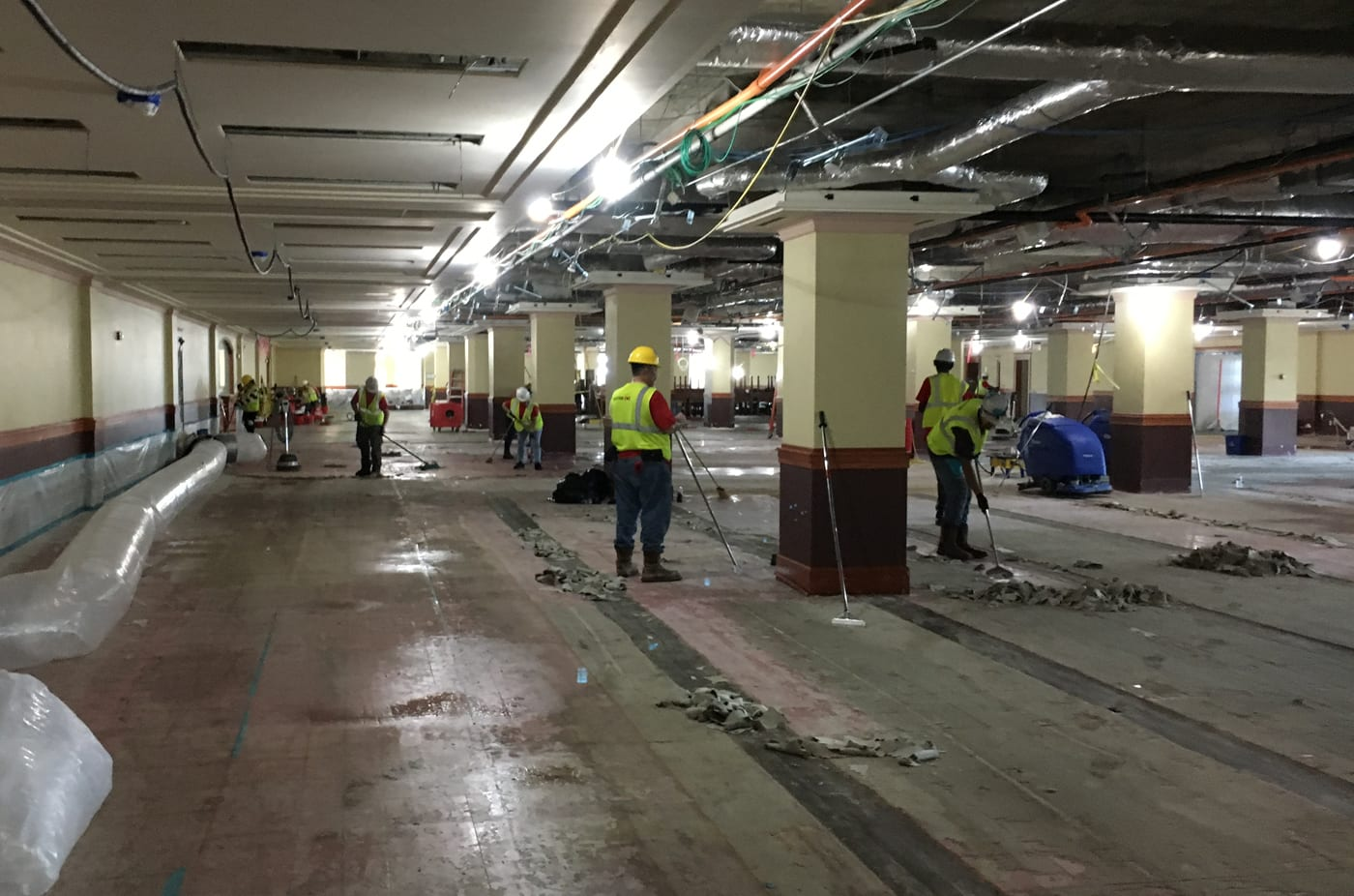Eight workers in hard hats and yellow construction vests are stationed across the entire length of the floor wielding long-handled scraping tools.