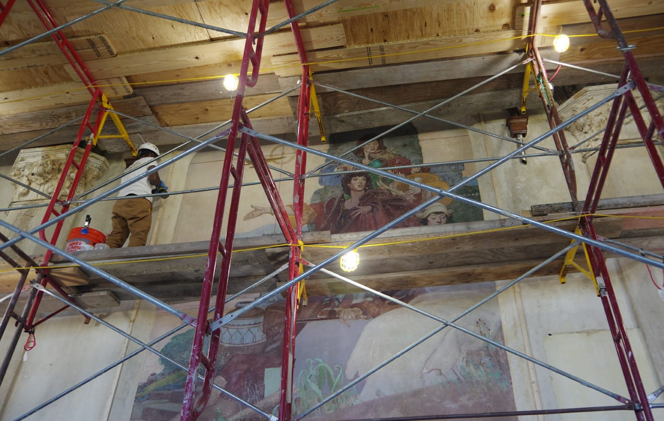 At left, a worker in a white hard hat stands elevated on a rough wood floor supported by scaffolding. An allegorical mural depicting the arts is to his right.