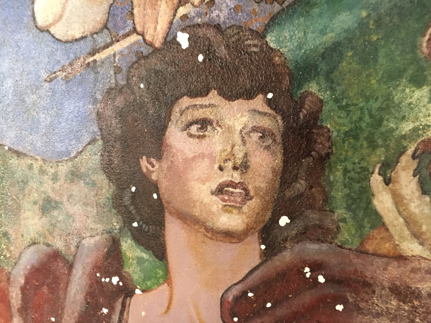 An art deco style painting of a figure with curling brown hair