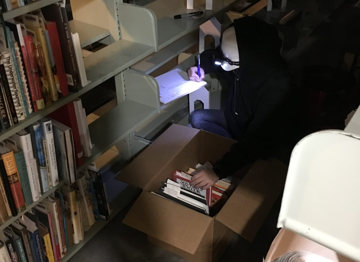 Next to a long row of bookshelves, a worker wearing a black hooded jacket and a headlamp over a white construction hat kneels while placing a cookbook in a box with one hand and taking notes with the other.